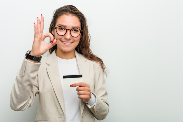 Young european business woman holding a credit card