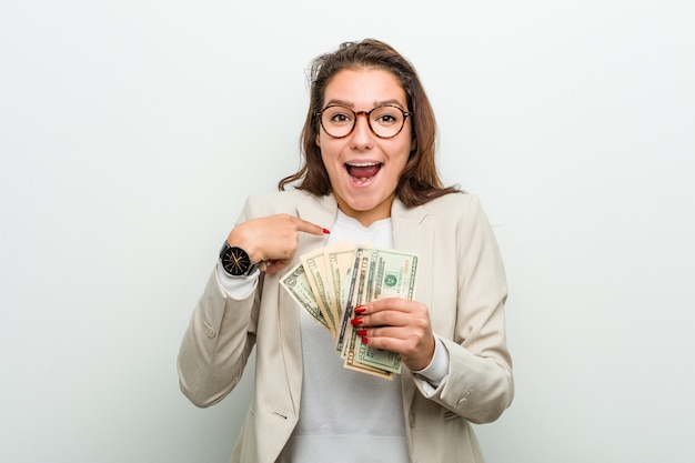 Young european business woman holding dollar banknotes surprised pointing at herself, smiling broadly.
