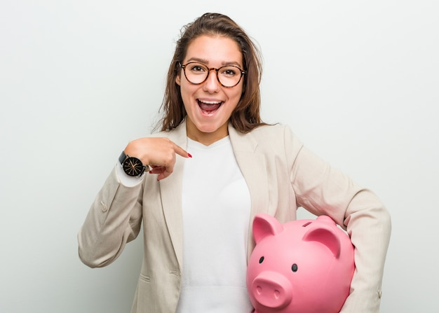 Young european business woman holding a piggy bank surprised pointing at herself, smiling broadly.