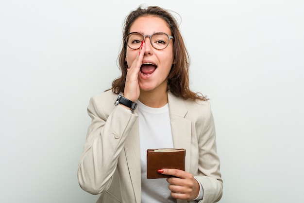 Young european business woman holding a wallet shouting excited to front.