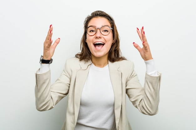 Young european business woman receiving a pleasant surprise, excited and raising hands.