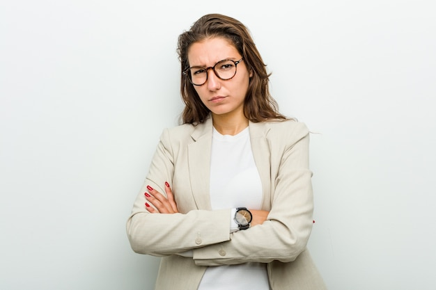 Young european business woman unhappy with sarcastic expression.