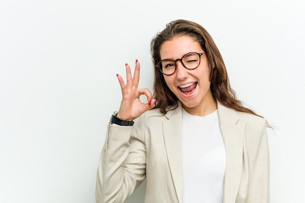 Молодая европейская бизнес-леди подмигивает и держит рукой жест.