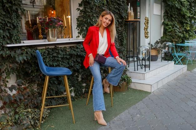 Giovane donna europea sicura di sé con candido sorriso in posa all'aperto nel bar