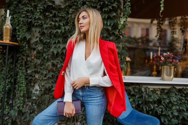 バーで屋外ポーズ率直な笑顔で若いヨーロッパの自信を持って女性。赤いおしゃれなジャケットを着て