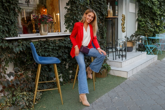 Молодая европейская уверенная в себе женщина с откровенной улыбкой позирует на открытом воздухе в баре