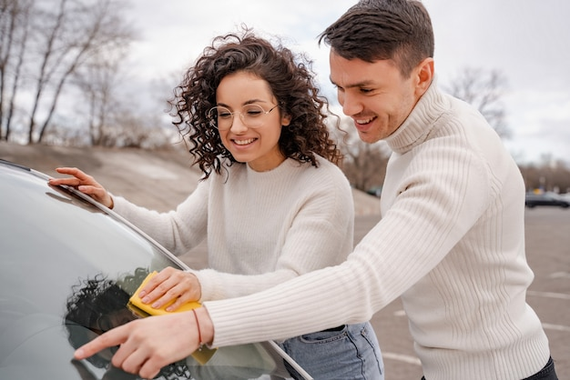 Young european couple cleaning car windshield with rag. man pointing with finger on glass for curly girl. persons happy and smiling. concept of enjoying time together