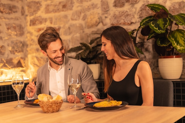 Young european couple having dinner in a beautiful restaurant, celebrating valentine's day
