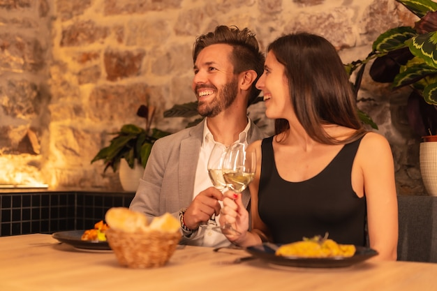 A young european couple toasting drinks while having dinner in a restaurant, celebrating valentine's