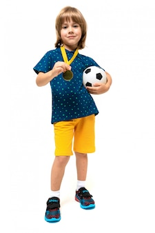 Young european cute child in sportswear stands and holds a soccer ball and a whistle on his neck on a white wall