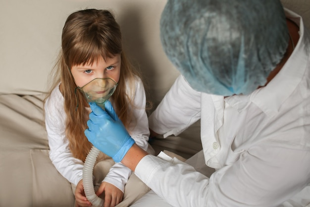 Young european doctor helping a little girl with a spray mask doctor applying inhalation medication therapy on little girl with inhalation therapy for asthma with inhaler mask