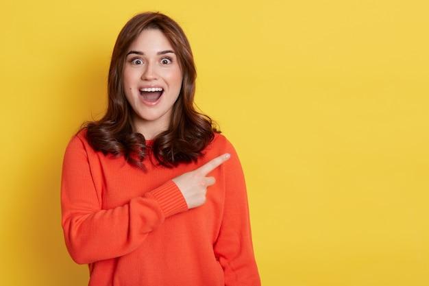 オレンジ色のセーターを着た若いヨーロッパ人の興奮した若いブルネットの女性の女の子、黄色の壁に孤立したポーズ、人差し指を脇に向けて口を開けた美しい女性。