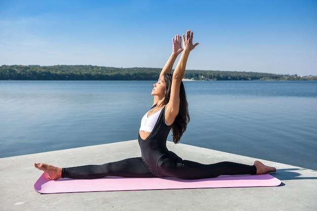Молодая европейская спортсменка делает упражнения на растяжку ног, сидит на шпагате на улице у озера. здоровый образ жизни