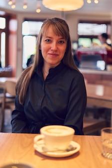 Молодая европейская женщина смотрит в камеру за столом в кафе с чашкой капучино в кофейне