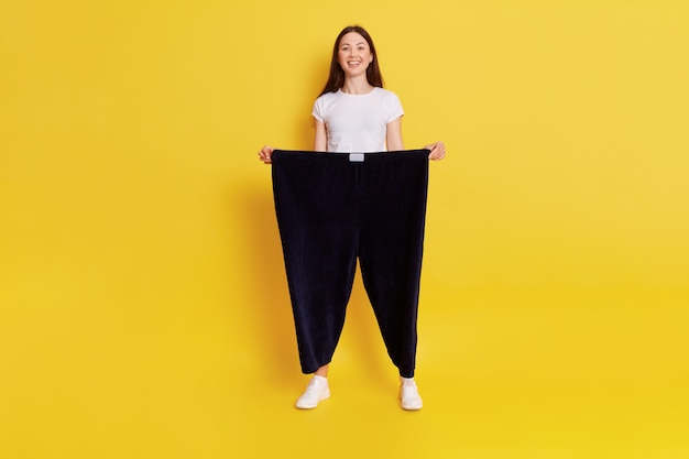 Young european female with dark hair wearing casual white t shirt and black pants too big size, adorable happy woman loose weight, feels great, expressing positive, keeps hands in trousers.