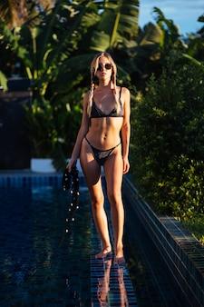 Giovane donna sottile in forma europea con due trecce in bikini nero lucido alla moda sul bordo della piscina