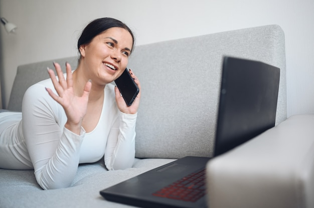 Young european freelance woman making a selfie or video call laptop and phone on grey couch during coronavirus isolation home quarantine. covid-19 pandemic corona virus. online work from home concept.