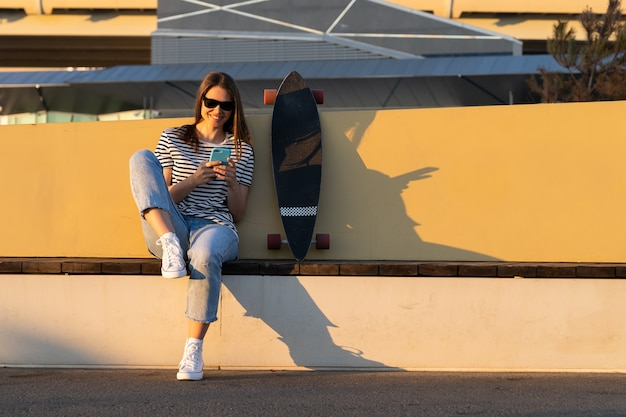 Young european girl chat using smartphone application sitting with longboard skate in park at sunset