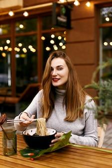 Young european girl eating ramen
