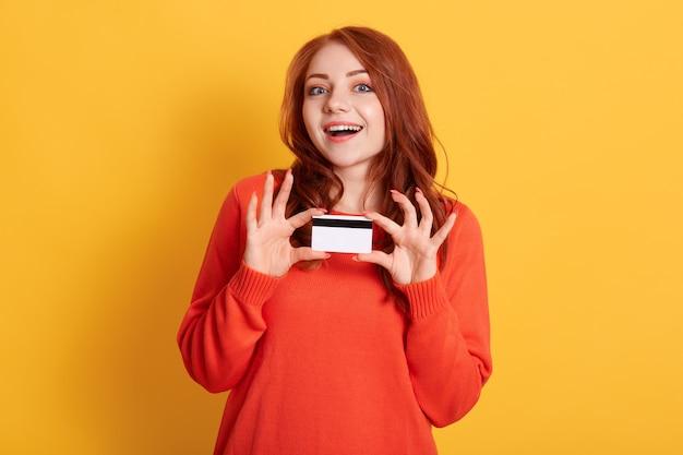 Молодая европейская девушка держит кредитную карту, изолированную на желтом пространстве