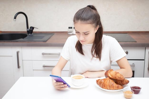 젊은 유럽 소녀는 아침에 아침에 스마트폰으로 뉴스를 읽습니다 프리미엄 사진