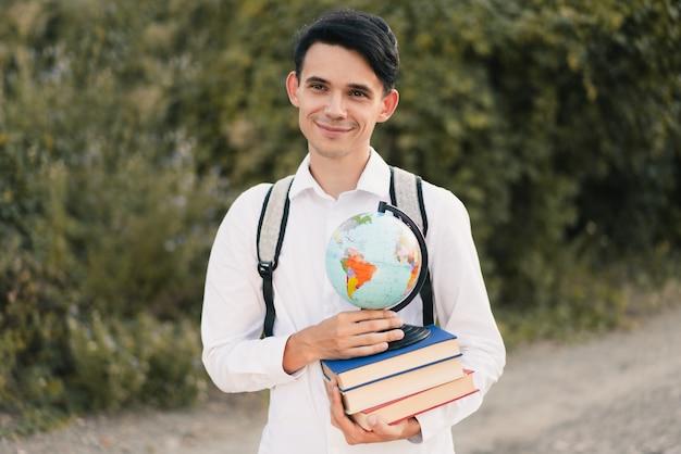 彼の背中に灰色のバックパックと白いクラシックシャツを着た若いヨーロッパ人は、地球と緑の自然に対してかわいい笑顔で教育本のスタックを保持しています。教育コンセプト
