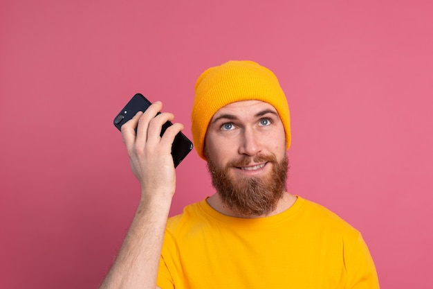 핑크에 스마트 폰을 사용하여 행복 듣는 오디오 메시지를 웃는 젊은 유럽 잘 생긴 남자
