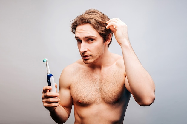 Young european man holding electric toothbrush. handsome muscular guy with naked sportive torso touching his hair. concept of hair care and hygiene. isolated on beige background. studio shoot