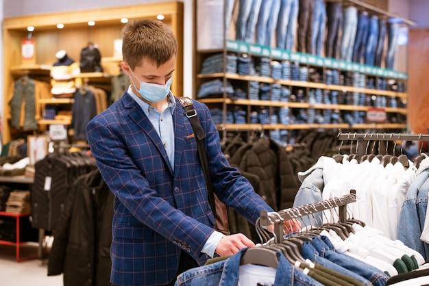 医療マスクの若いヨーロッパ人は、モールで買い物をして、店で物事を選びます