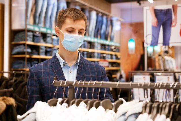 의료 마스크에 젊은 유럽 남자는 쇼핑몰에서 쇼핑, 상점에서 물건을 선택