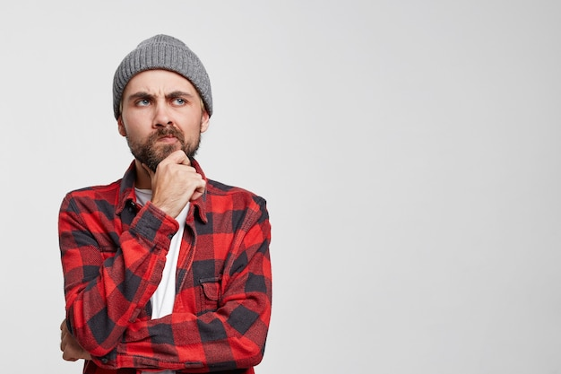 Young european man thinks, raised hand to face, touches his beard, looks dissatisfied