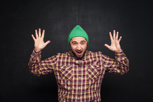 Young european man with beard in green knitted hat , looks surprised and puzzled. showing fingers upwards and right side. black background, blank copy space for text or advertisement