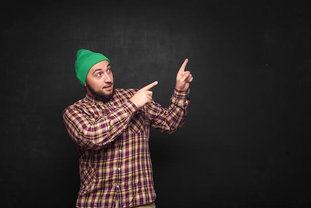 緑のニット帽をかぶったひげを持つ若いヨーロッパ人は、驚いて困惑しているように見えます。指を上向きと右側に表示します。黒の背景、テキストまたは広告用の空白のコピースペース