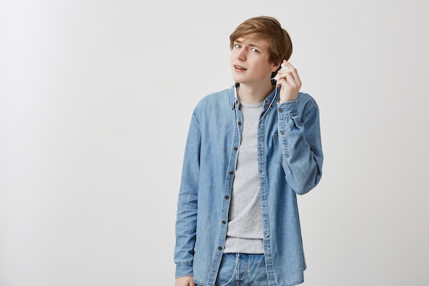 Young european man with fair hair in denim shirt, listens to music on mobile phones, wearing white earphones. young male enjoys favourite songs, uses wifi. modern techologies concept