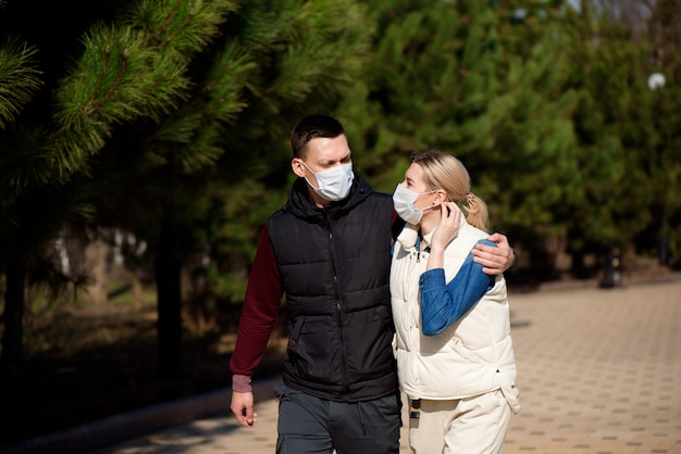 Young european man and woman in protective disposable medical mask walking outdoors afraid of dangerous ncov 2019 influenza coronavirus mutated and spreading in china