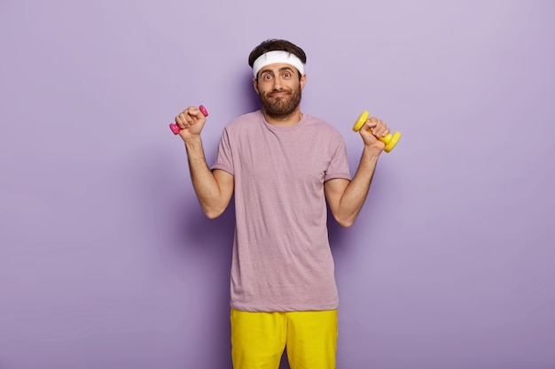 Young european man works on muscles, raises arms with dumbbells, has exercises indoor, has athletic body, dressed in purple t shirt and yellow shorts, stands indoor, has funny look, dark bristle