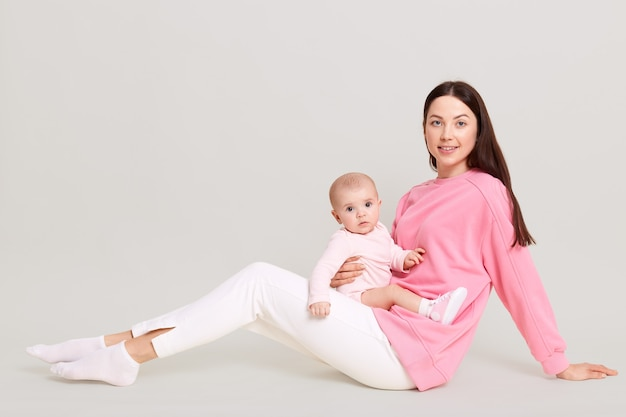 Young european mom sitting on floor with her little daughter in her arms, baby in bodysuit on mother's legs, female wearing white pants and pink sweatshirt posing with infant against white wall.
