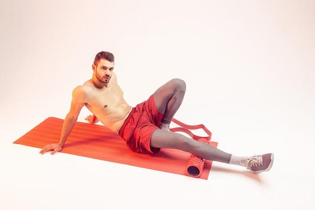 Молодой европейский спортсмен делает упражнения с массажным роликом на фитнес-коврике. красивый бородатый мужчина с голым спортивным торсом и глядя в камеру. изолированные на бежевом фоне. студийная съемка. копировать пространство
