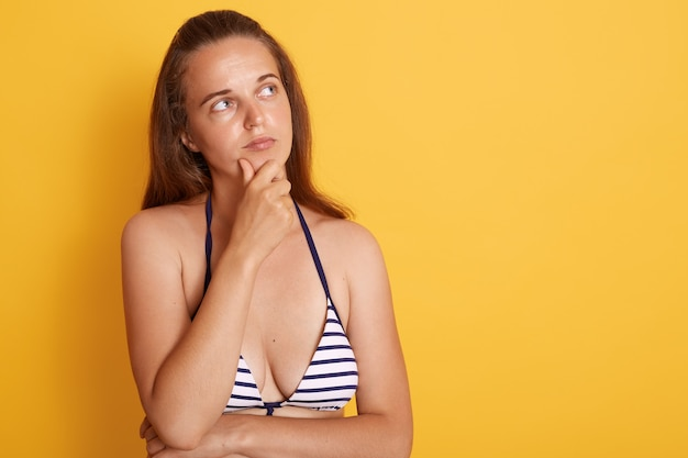 Young european swimmer woman isolated over yellow wall, looks pensive, looking at copy space with thoughtful facial expression, dresses striped swimsuit..