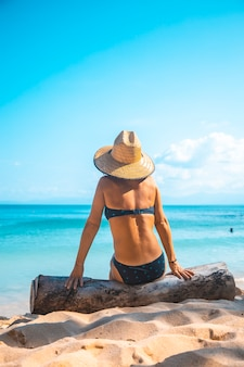 A young european tourist with a hat sitting on a log on the beach of punta sal in tela