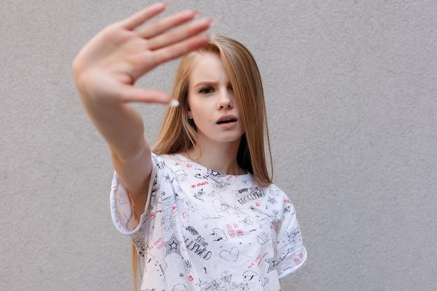 白い背景の上に隔離されたカメラから彼女の顔を隠そうとしている停止ジェスチャーで手を握って怒っている不満の表情を持つ若いヨーロッパのトレンディな女性。有名なモデルになるのは難しいです