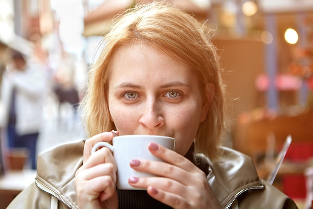 Young european woman drinking coffee in street cafe during cold weather.