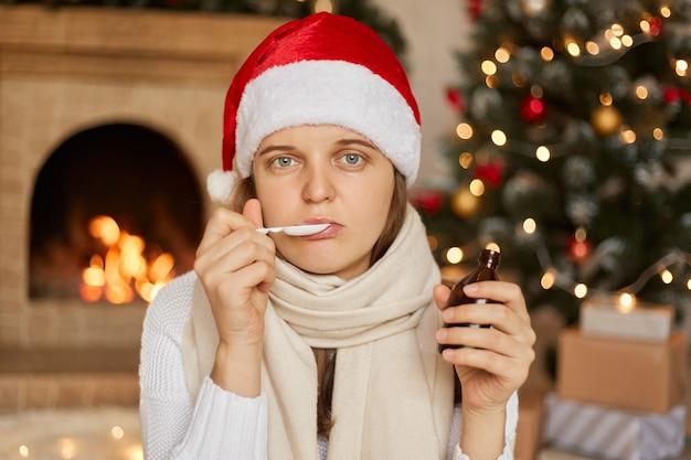 Молодая европейская женщина пьет лекарство из ложки, в шляпе санта-клауса и шарфе, позирует в одиночестве в помещении с камином и рождественской елкой.