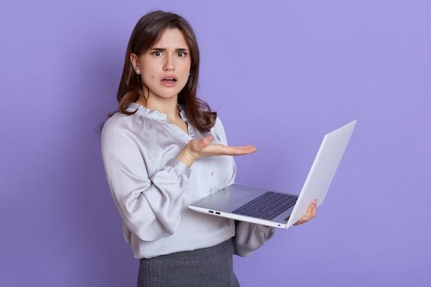 コンピュータの操作上の問題に不満を抱き、困惑して驚いた表情をしたヨーロッパの若い女性は、手のひらでノートパソコンの画面を指差して、予期しない問題を抱えています。