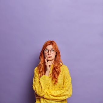Young european woman in glasses with natural red hair stands in thoughtful pose tries to choose something or thinks about future concentrated above.