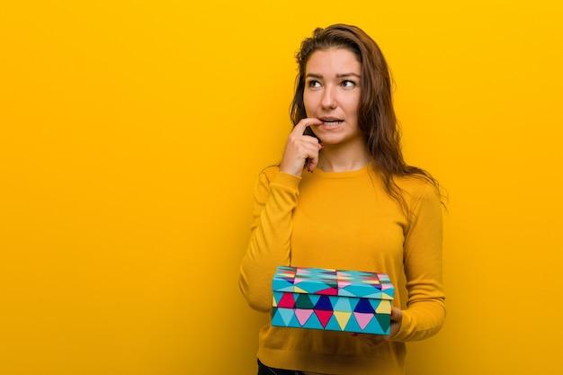 贈り物を持っている若いヨーロッパの女性は、コピースペースを見ている何かについて考えてリラックスしました。