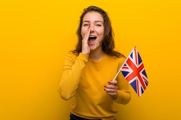 Молодая европейская женщина, держащая флаг соединенного королевства, кричит, возбуждена вперед.