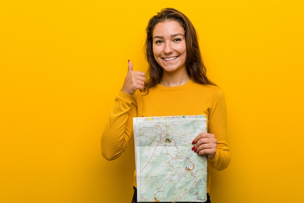 Young european woman holding a map smiling and raising thumb up