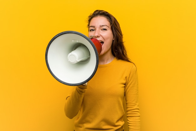 Young european woman holding a megaphone shouting excited to front.