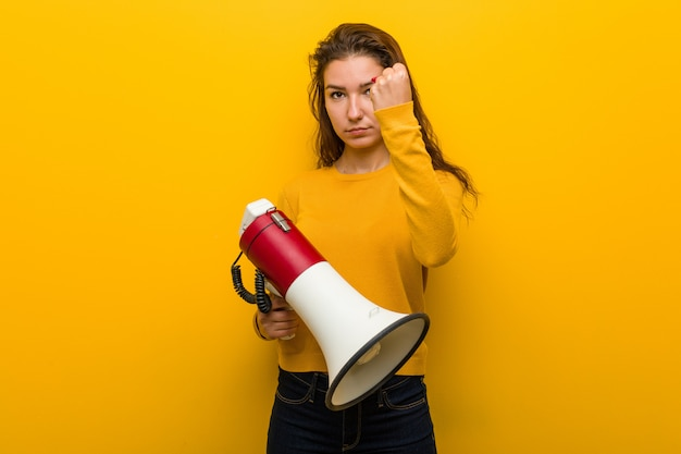 Young european woman holding a megaphone showing fist